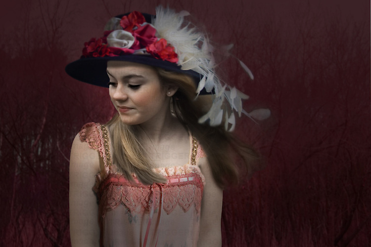 Young woman against a dark background, wearing old fashioned clothes, looking down reflecting