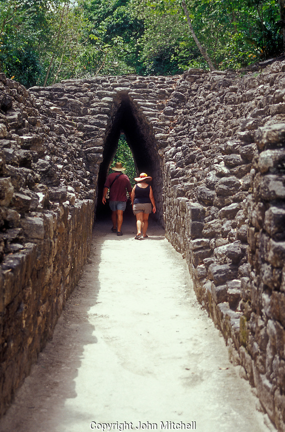 Tourists walking through a Mayan corbeled archway at the Becan archaeological site, Campeche state, Mexico