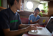 Sakyo Noda (on left of image), campaigner, and Daisuke Miyachi (on right of image, wearing glasses), logistics person, both from Japan, at work on the Greenpeace ship 'Rainbow Warrior', in transit heading towards Fukushima, Japan on Friday April 22nd 2011.