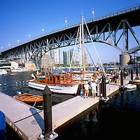 Vancouver, BC, British Columbia, Canada - Historic Wooden Boats docked in False Creek at Granville Island, under Granville Street Bridge