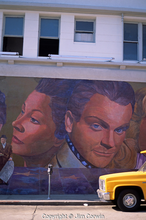 Mural painted on a side of building depicting stars of old Hollywood, along street with yellow pick up truck Hollywood Los Angeles California USA