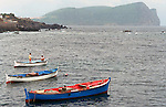Two boys sit in a fishing boat in the shadows of Monte Brasil onTerceira, Azores. Fishing is one of the main industries for residents on these islands. Far out in the Atlantic Ocean, some 850 miles off the western coast of Lisbon, Portugal lies the 425-mile long archipelago of the Azores. (Jim Bryant Photo).....