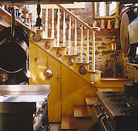 The staircase leading up from the basement kitchen is lined with antique copper pots