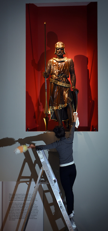 EVIE JEFFREYS, EXHIBITION TEAM, GIVES A FINAL DUSTING TO A STATUE OF A BARON ON LOAN FROM THE HOUSE OF LORDS. PART OF THE BRITISH LIBRARY'S MAGNA CARTA: LAW, LIBERTY,LECACY EXHIBITION OPENING ON MARCH 13TH.PHOTO BY CLARE KENDALL. FOR FURTHER INFO CONTACT PRESS OFFICE 02074127110