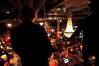 Two plain clothed police officers watch a crowd a a busy restaurant.<br /> <br /> Stig Gaustad og Morten Haukeland fra Sentrum Politistasjons etteretningsavdeling f&oslash;lger med p&aring; utelivet i Oslo sentrum. . (Foto:Fredrik Naumann/Felix Features)