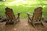 Stock Photo of two Empty Old Wooden Adirondack Chairs Facing a Sun Dappled Green lawn