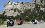 STURGIS, SOUTH DAKOTA - AUGUST 2010:  Motorcyclists ride near Mount Rushmore in the Black Hills of South Dakota while attending the 70th annual Sturgis Motorcycle Rally.  The attendance estimates were placed between 500, 000 and 700,000 bikers.