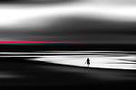 Conceptual beach scene with lone figure walking across sand