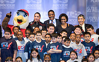 First Lady Michelle Obama poses with the assembled crowd, including US Soccer President and CEO Ed Foster-Simeon, DC United owner Will Chang, and the mascot of the Washington Freedom, Glory,  during a US Soccer Foundation clinic held at City Center in Washington, DC.