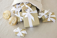 A variety of Christmas parcels tied with ribbon and gold baubles tumble out of a Christmas stocking