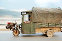 Three wheeled tuk tuk truck moving down road, Yangshuo, Guanxi, China