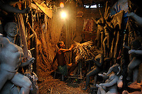 INDIA (West Bengal - Calcutta)  2006, A idol maker at work in his studio at Kumortuli. Kumortuli in North Calcutta is the hub of Durga idol makers. During the other time of the year the artists engage themselves in prepairing other idols and masks depending on the assignments. But the most of the earning they aquire from making Durga idols. A Durga idol can cost up to 7000 usd. Which is a big price in Indian Currency.  Durga Puja Festival is the biggest festival among bengalies.  As Calcutta is the capital of West Bengal and cultural hub of  the bengali community Durga puja is held with the maximum pomp and vigour. Ritualistic worship, food, drink, new clothes, visiting friends and relatives places and merryment is a part of it. In this festival the hindus worship a ten handed godess riding on a lion armed wth all possible deadly ancient weapons along with her 4 children (Ganesha - God for sucess, Saraswati - Goddess for arts and education, Laxmi - Goddess of wealth and prosperity, Kartikeya - The god of manly hood and beauty). Durga is symbolised as the women power in Indian Mythology.  In Calcutta people from all the religions enjoy these four days of festival in the moth of October. Now the religious festival has become the biggest cultural extravagenza of Calcutta the cultural capital of India. Artistry and craftsmanship can be seen in different sizes and shapes in form of the idol, the interior decor and as well as the pandals erected on the streets, roads and  parks.- Arindam Mukherjee