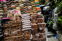 Blocks of panela (a solidified juice of sugar cane) for sale seen on the market in Quito, Ecuador, 5 October 2012. Panela, a solid block of raw, unrefined sugar, is made by cooking and evaporation of the sugar cane juice into a golden, sticky syrup which is then poured into the wooden molds and allowed to solidify. Having the taste like a cross between molasses and brown sugar, panela is served as a hot or cold infusion (aguapanela). Due to the large amounts of proteins, vitamins and minerals, panela is believed to have healing powers.