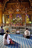 Myanmar, Burma, Yangon.  Sule Pagoda.  Early-Morning Worshipers Praying at Buddha Shrine.