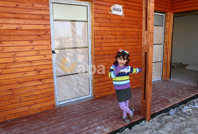 A Palestinian girl plays outside her house donated by a charity organisation as temporary housing for those whose houses were destroyed during a seven-week Israeli offensive, in Khuzaa, east of Khan Younis, in the southern Gaza Strip, on March 01, 2015. Photo by Abed Rahim Khatib