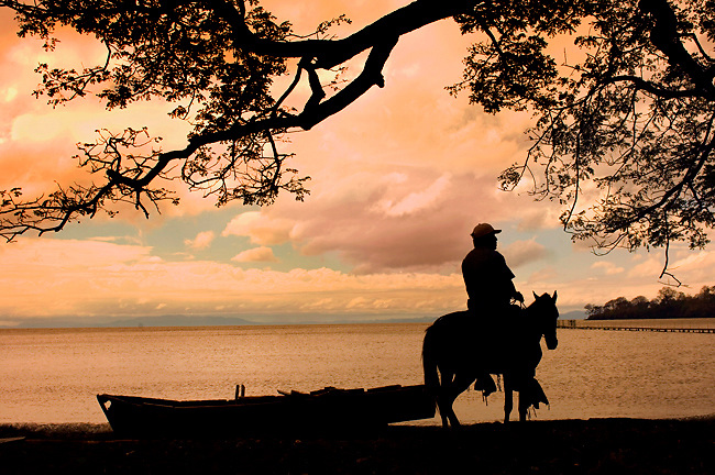 Resident of Ometepe Island brings his horse down by Lake Nicaragua at sunrise.  Ometepe is an island formed by<br /> two volcanoes rising from Lake Nicaragua.  The island has been declared a UNESCO Biosphere Preserve.