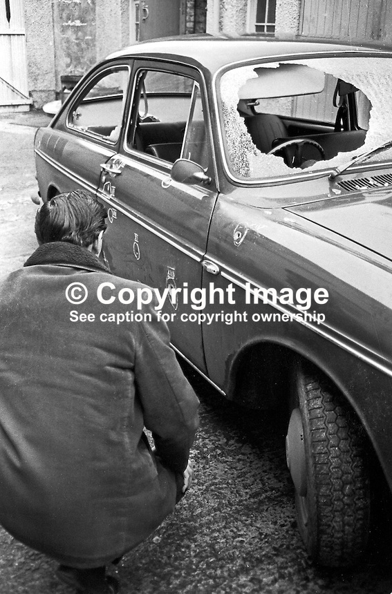 A detective at Dundonald RUC station, N Ireland, examines the vehicle in which Jack Mooney was killed and two colleagues, all Roman Catholics, were travelling when they arrived to start the night shift at the local Rolls-Royce factory. The UDA/UFF gun attack was on New Year's Day 1973, 1st January 1973. Jack Mooney, 31 years, was married with 2 children. His 62 year old father, Hugh Mooney, was among the passengers travelling in the vehicle. For more information see Lost Lives 728. 197301010002b<br />