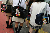 Young schoolgirls all displaying their latest trend, that of Disney characters on their school bags, near '109 Building', Shibuya, Tokyo, Japan.