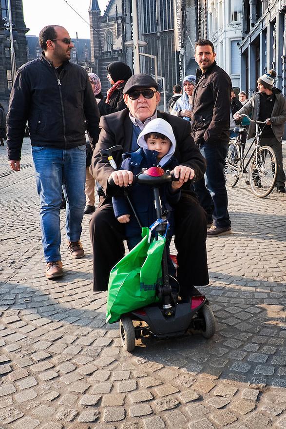 Nederland, Amsterdam, 19 maart 2015<br /> Buitenlandse toerist in scootmobiel op de Dam. Kleinzoon mag lekker meerijden met opa. <br /> <br /> Foto: Michiel Wijnbergh
