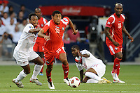 Anibal Godoy (20)  midfielder Panama goes pass Justin De Guzman (6) Canada...Canada and Panama tied 1-1 in Gold Cup play at LIVESTRONG Sporting Park, Kansas City, Kansas.