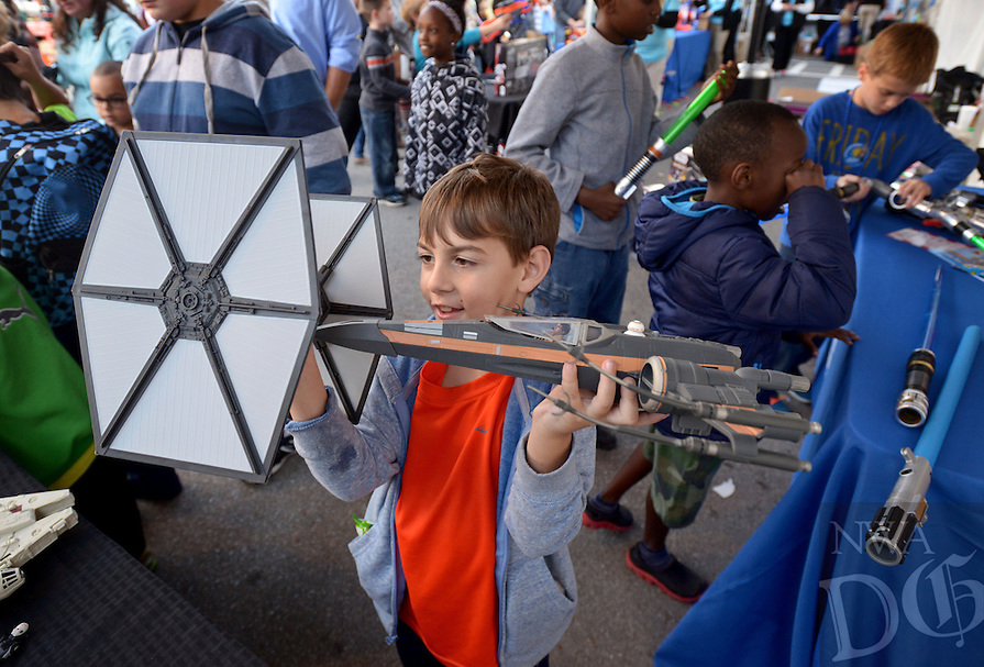 NWA Democrat-Gazette/BEN GOFF @NWABENGOFF<br /> Josh Cessario, 8, plays out a dogfight with a Tie Fighter and X-Wing in the Hasbro booth on Friday Nov. 6, 2015 during Downtown Bentonville, Inc.'s First Friday: Toyland on the Bentonville Square. Walmart toy vendors displayed a variety of their new offerings at the event ahead of the holiday shopping season.