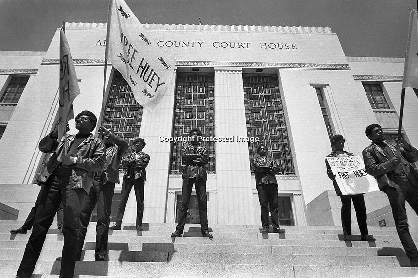 Black Panthers standing on the steps of the Alameda County court housein Oakland California protesting &quot;Free Huey&quot; Newton who is jailed inside. (copyright @<br /> (photo 1968)( by Ron Riesterer)