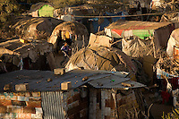 This sprawl of homes made from sticks, cardboard and  tattered remains of clothing is home to  29,000 people in Hargeysa, Somaliland. .Originally  State House was the seat of Britain's colonial governement in  Somaliland. During  the late 1980's   the building along with the rest of Hargeysa was bombed at the start of Somalia's civil war..When the governemnet of Said Barre fell  people returned from refugee camps in Ethiopia to Hargeysa. Many buildings had been completely destroyed and  those with outshelter began to settle in and around the  State House building..Even now families are  arriving for safety from Mogadishu..