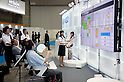 May 131, 2012, Tokyo, Japan - Japanese woman staff talks about the innovations to the visitors. The Smart Grid Exhibition and Automotive Next Industry Fair 2012 shows the next generation of vehicles and manufacturing working with eco energy, from May 30th. to June 1st. at Tokyo Big Site. ..