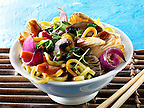 Oriental vegetarian stir fry of vegetables, noodle and mushrooms in a bowl with chop sticks