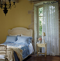 A French bed with fresh blue and white linen in a bedroom overlooking the garden
