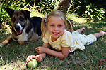 Young girl with ponytails rests in shade with her dog.