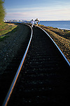 Young teens walking on railroad tracks Edmonds Beach Washington State USA