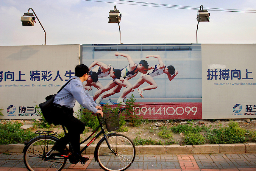 A man cycles past the Olympic Park construction site in Beijing, Wednesday, May 25, 2005. The city will host the Games in 2008.