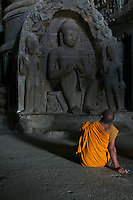Buddhist Monk inside one of the Ellora Caves Aurangabad, India.The famous Ellora caves are located in the lap of the Chamadari hills. These historical caves are regarded as world heritage and are situated 18 miles northwest of Aurangabad.  .A wonderful example of cave temple architecture, the world heritage Ellora caves own elaborate facades and intricately carved interiors. These carved structures on the inner walls of the caves reflect the three faiths of Hinduism, Buddhism and Jainism. These exotic caves were carved during 350 AD to 700 AD period. .Ellora caves are hewn out of basaltic rock of the Deccan trap, and are datable from circa 5th century A.D. to 11th century A.D. In all 34 caves were excavated here out of which Cave 1 to 12 are Buddhist, 13 to 29 are Brahmanical and 30 to 34 are Jaina.