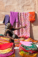 A vendor sells lengths of folded fabric in the local market