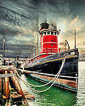Tug boat under dramatic sky moored in harbour
