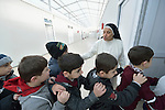 Sister Anahid, a member of the Dominican Sisters of St. Catherine of Siena, shepherds students into a classroom in a primary school she supervises in Dohuk, Iraq. Most of the students were displaced from their home villages when the Islamic State group took over portions of the Nineveh Plains in 2014. Because they came from communities with Arabic curriculum schools, they often don't fit well in schools in the villages where they resettled, because those schools teach in Kurdish or Assyrian. So the religious order started the school, which has students from several faiths, including Islam and Christianity. The Christian Aid Program Nohadra - Iraq (CAPNI) provides transportation for many students to Dohuk from the rural villages where their families have taken refuge.