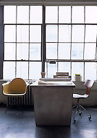 A functional desk beside industrial windows is teamed with designer chairs in this home office