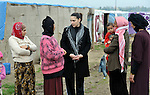 Sabeen Abdulsater (center, in black coat), project officer for the Bekaa Valley for International Orthodox Christian Charities, talks with women refugees from Syria in the village of Jeb Jennine, Lebanon.