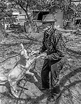"""December 1971:  Modesto, California—Dad Walkling— Dad plays with kid goat in his back yard.  I first met Orlando """"Dad"""" Walkling at his house in the airport district of Modesto just before his 104th birthday.  Walkling was born in Indian Territory January 2, 1868, near a town now called McAlester, Oklahoma.  His mother was Shawnee and his father, whom he didn't remember, was an Englishman named Orlando.  He later used the name Walkling instead of his Indian name of Skipocase.  On September 16, 1893, Skipocase O. Walkling, then 25 years old, was among thousands of settlers who rode into the Cherokee Strip Land Run of Oklahoma to make a free land claim.  Walkling told of how he rode into the 226-mile long """"Strip"""" to claim 160 acres.  """"There were thousands of men who waited at the line until noon that day.  The army gun was fired and chaos broke out. Every man carried a gun. There was no law, no sheriff, nothing.  People had to fight for their claim even though they were first.""""  Walkling made a claim, but later gave it up when he had a chance to farm a piece of land in Noble County, Oklahoma.  He cleared the land with six yoke of oxen and planted peach orchards.  He and his first wife ran a combination grocery store and hotel there.  He had nearly 1,000 trees and began a cannery to process the crops.  """"One day when the train came in a woman dressed like a Salvation Army woman handed me a bundle as I stood on the ramp, then she jumped back into the train.  I opened it and there was a pair of twins, a boy and a girl,"""" Walkling said.  He and his wife did not have children, so they adopted the twins legally and raised them.  He said they raised six others but did not adopt them.  He came to Modesto in 1944 at 76 years of age and went to work for a meat firm before he opened a poultry store.  After that store closed, he made bullwhips and wove rope for truckers at his home.  In 1968, Dad Walking, then 100 years old, visited Oklahoma for the 75th anniversary of the"""