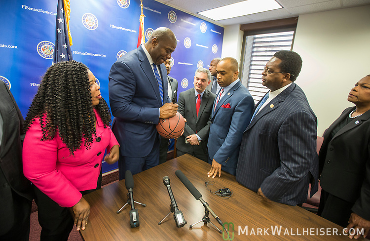 "Earvin ""Magic"" Johnson, retired professional basketball player and current president of operations for the Los Angeles Lakers of the NBA, signs a baseball after a meeting with the Florida Senate Democratic Caucus  about health care at the Florida Capitol in Tallahassee Florida March 13, 2017."