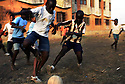 """Ivorian boys wearing plastic shoes called """"korodjo"""" play a game of street football in a poor district of the Port Bouet neighborhood of Abidjan, Ivory Coast February 17,2006. Football is an integral part of the social fabric that makes up Ivorian society."""
