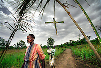 People on their way to church walk under arched palm leaves and a hanging palm cross to mark Palm Sunday.