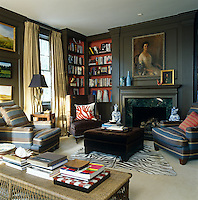 A formal portrait is the focus of the panelling above the fireplace in the family room
