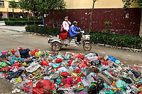 A woman drives her grandchild past a garbage heap at a housing project in Liaocheng city in the northeastern Chinese province of Shandong. They were all moved from their farmland and resettled nearby in this purpose-built estate. The Chinese government plans to move 250 million rural residents into urban areas over the coming dozen years though it is unclear whether people want to move and where the money for this project will come from. Further urbanisation is meant to drive up consumption to counterbalance an export orientated economy and end subsistence farming but the drive to get people off the land is causing tens of thousands of protests each year. /Felix Features