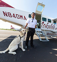 A Mokulele Airlines pilot poses with a canine passenger at an airport in Hawai'i.