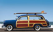side view of woody car with surfboard and surf in background