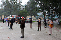 A Tai Chi class near the Lenin statue in Duong Dien Bien Phu Street, Hanoi, Vietnam.. For a county not know for it's sporting prowess, Hanoi, Vietnam's capital, appears to be gripped in a fitness frenzy. Before 6am street corners, parks and lake sides are a hive of activity as keep fit classes, Tai chi and personal exercise regimes are seen in abundance around the city. Particularly noticeable are Women's keep fit classes, often accompanied by loud poor quality western disco beat music as the occupants of the city get fit come rain or shine. Hanoi, Vietnam. 18th March 2012. Photo Tim Clayton