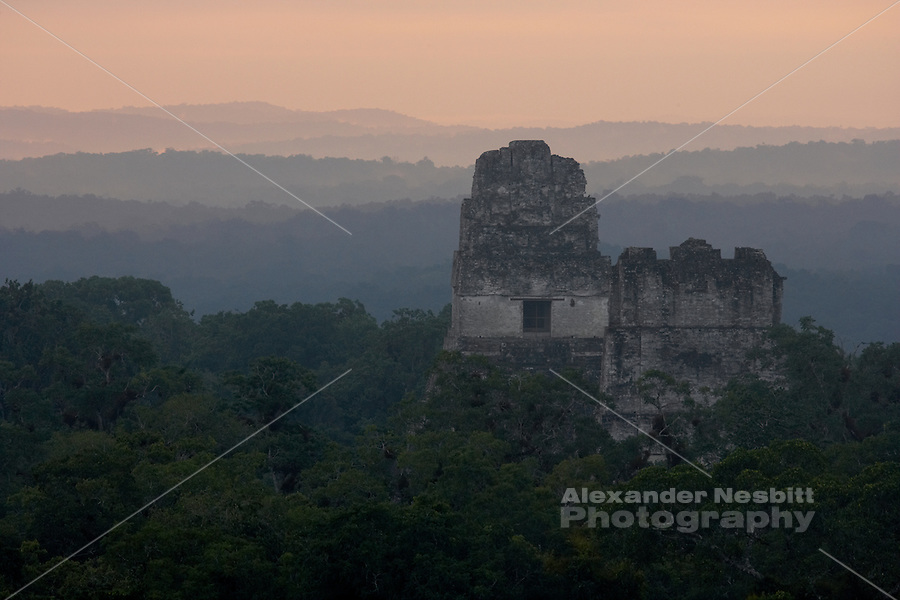 Tikal, Guatemala - Sunrise brightens layers of mist over Temple I and Temple II at the classic Maya (A.D.250-900) site of Tikal. The Temples rise above the jungle canopy in the view east from atop Temple IV, the highest standing ancient structure in the New World.