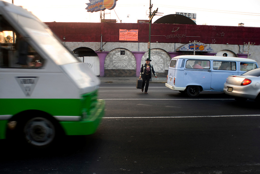 A Norteño musician cross the busy Eje Central on his way to Plaza Garibaldi where Mariachis gather to be hired in Mexico City, Friday, Jan. 4, 2008